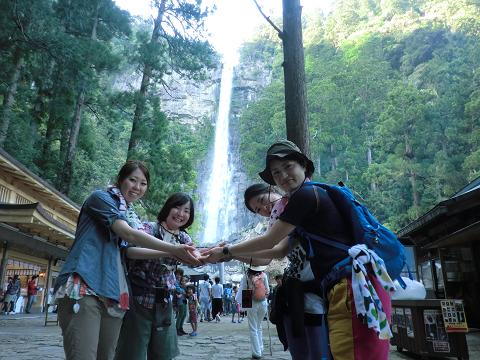 那智の滝を受け止めるポーズをする女子旅4人
