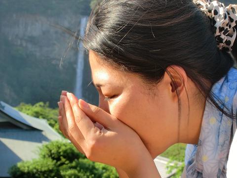 那智の滝の水を飲むポーズをするツアー参加女性