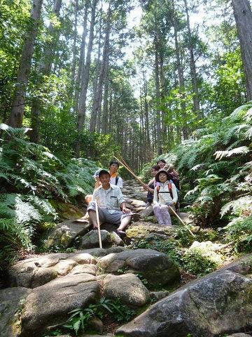 熊野古道伊勢路・馬越峠の石畳に座るツアー参加の家族