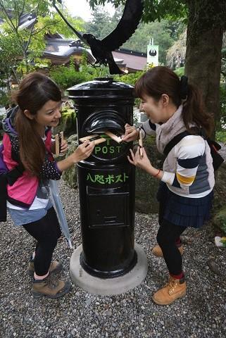 熊野本宮大社の八咫ポストに投函するツアー参加女性2人