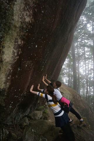 天狗倉山の大石を押すツアー参加女性2人