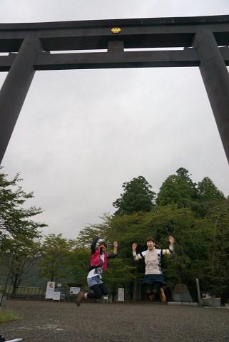 大斎原の鳥居の下でジャンプするツアー参加女性2人