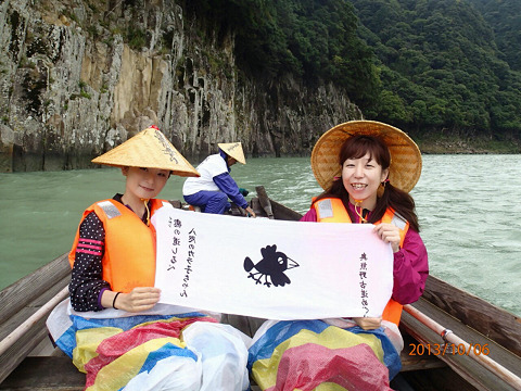 熊野川舟下りに乗船して手拭いを広げるツアー参加女性