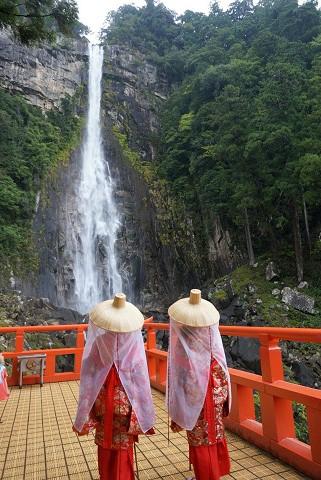 那智の滝の前で平安衣装を着たツアー参加女性2人