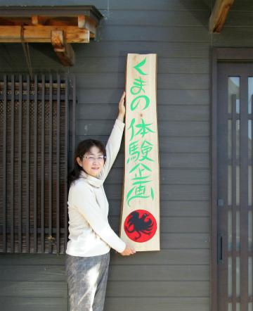 番留京子作・くまの体験企画看板を持つ内山裕紀子