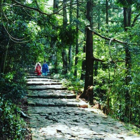 熊野古道大門坂の石畳を平安衣装体験の夫婦が歩く