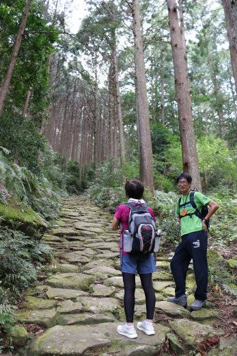 熊野古道伊勢路・馬越峠の石畳にてガイドの西尾寛明と女性参加者