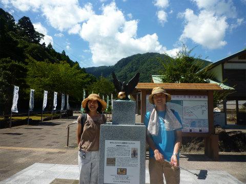 大門坂駐車場の八咫烏石碑で記念写真を撮るツアー参加の夫婦