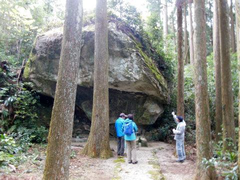 御浜町阪本の岩洞院にて説明する語り部ガイドの清水鎮一とツアー参加者2名