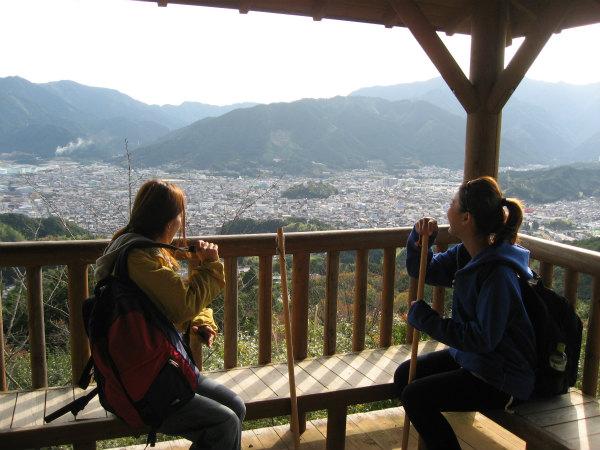 熊野古道伊勢路・馬越峠エコツアーにて展望台から尾鷲市を眺める女性参加者2人
