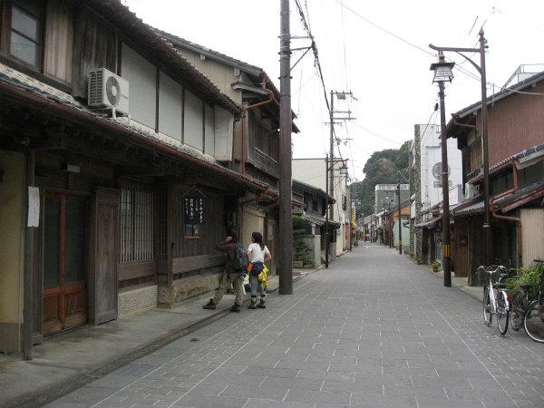 熊野市木本町の街道を歩くガイドと一人旅女性