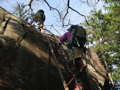 天狗倉山の梯子を上るツアー参加女性