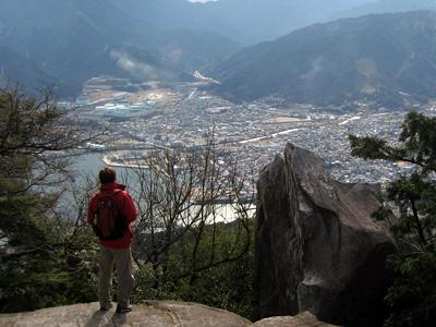 天狗倉山から尾鷲市を眺める一人旅男性