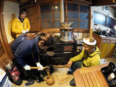 三木浦ゲストハウスで薪を割るオーナーと宿泊客