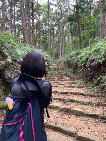 熊野古道中辺路と女性の後ろ姿、リュックからぬいぐるみが顔を出している